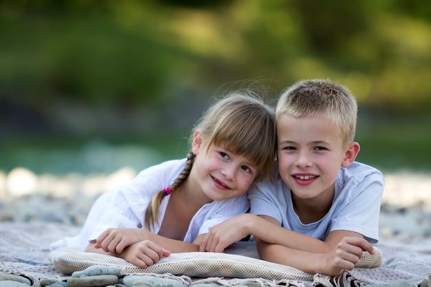 2 молодых счастливых милых белокурых усмехаясь класть детей, мальчика и девушки, брата и сестры обнял на галечный пляж на запачканный яркий солнечный летний день. дружба и идеальный праздник концепции.