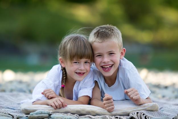 Две молодые счастливые милые белокурые улыбающиеся дети, мальчик и девочка, брат и сестра лежат на галечном пляже
