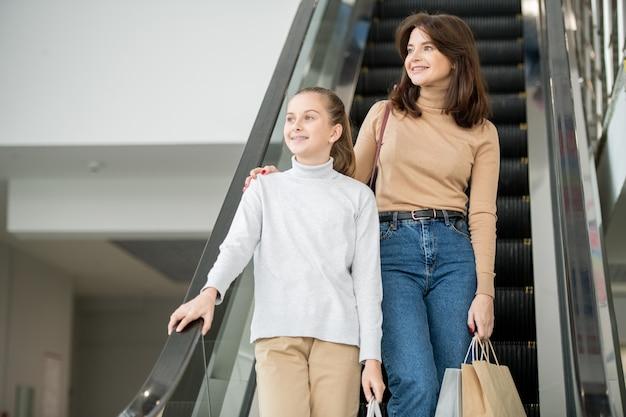 쇼핑 후 아래쪽으로 이동하는 동안 에스컬레이터에 서 캐주얼웨어에 두 젊은 행복 여성 쇼핑 중독자
