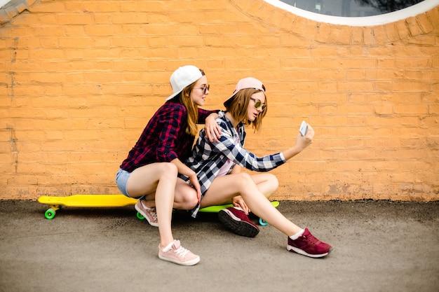 Hipster 옷 longboards에 앉아서 휴대 전화에서 selfie를 만드는 두 젊은 행복 한 여자 친구.