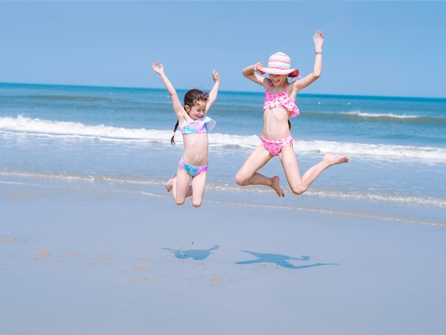 Two young happy girl  jumping into the air on the sea coast