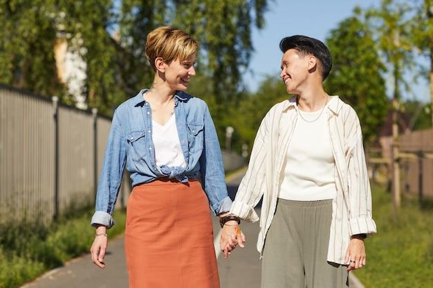 公園を歩いている間、お互いに笑顔で手をつないでいる2人の若い幸せなガールフレンド