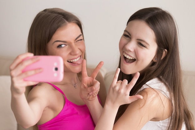 Two young happy girlfriends taking selfie with smartphone.