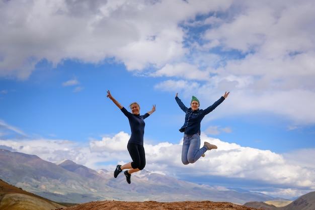 Две молодые счастливые девушки прыгают, поднимая руки вверх, с захватывающим видом на горы.