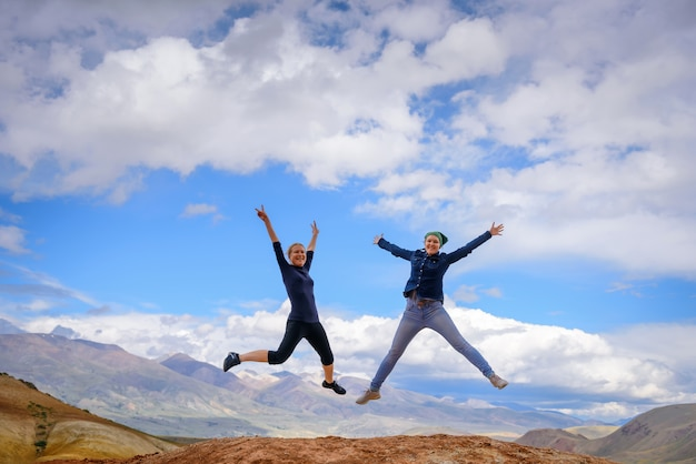 Two young happy girls jump raising hands up with spectacular view of mountains