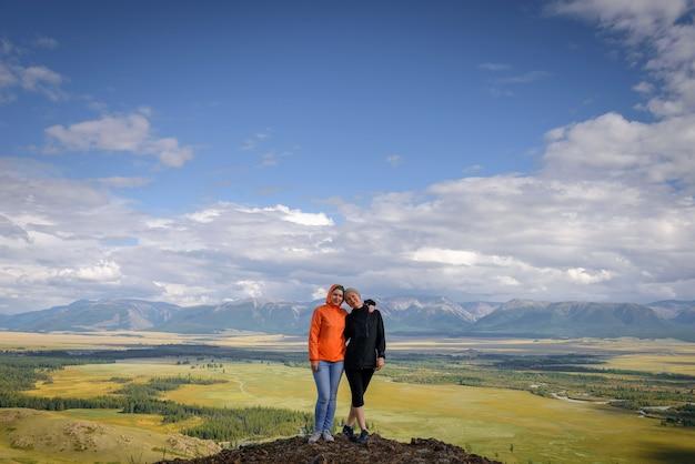 抱き締めて笑顔の丘の上に立っている2人の若い幸せな女の子。女性旅行者は、美しい山の風景を背景に撮影されています。
