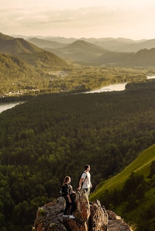 山の頂上にバックパックを持った2人の若い幸せなハイカーの男性と女性が谷の景色を楽しむ