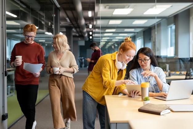 그들 중 하나가 태블릿 화면을 가리키는 동안 회의 프레젠테이션의 포인트에 대해 컨설팅 두 젊은 행복 이문화 경제인