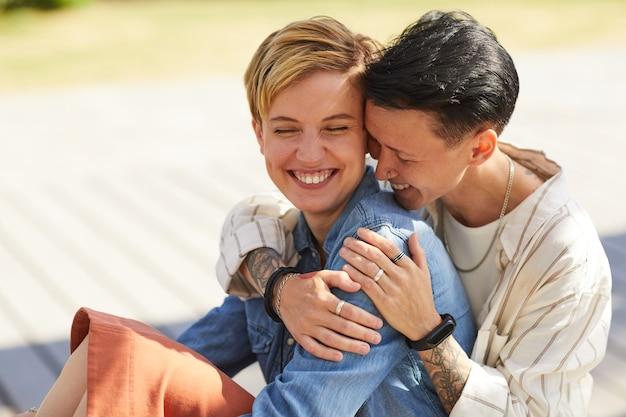 抱きしめて笑って屋外に座っている2人の若い幸せなレズビアン