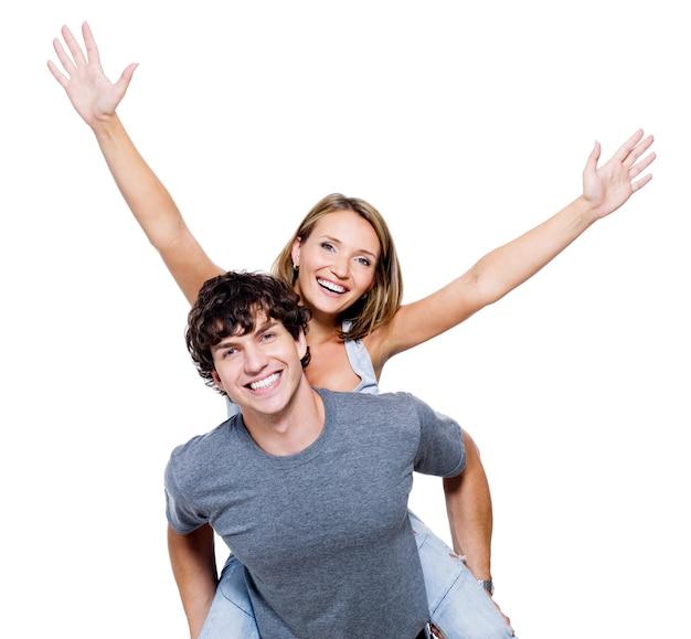 Два молодых счастливых человека с поднятыми вверх руками