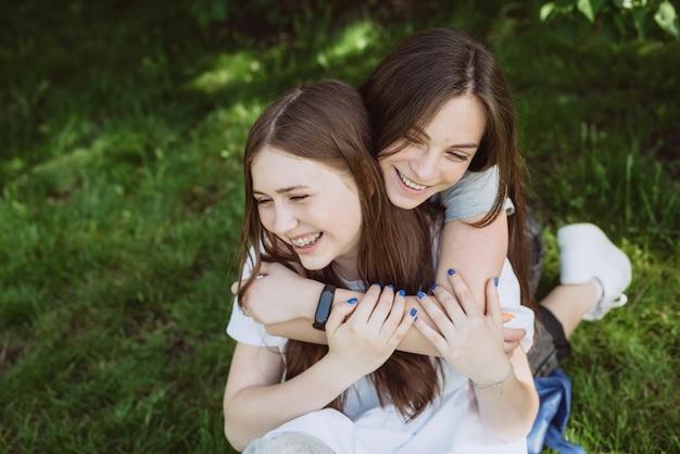 여름날 공원에서 재미 두 젊은 행복 십 대 소녀. 여성 우정입니다. 부드러운 선택적 초점입니다.