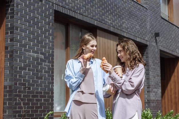 두 젊은 행복한 여자 친구가 도시 거리의 배경에서 크루아상과 커피와 함께 귀여운 이야기를 하고 웃고 있습니다.