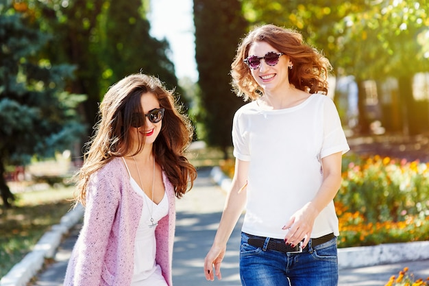 Two young happy women walking in the summer park