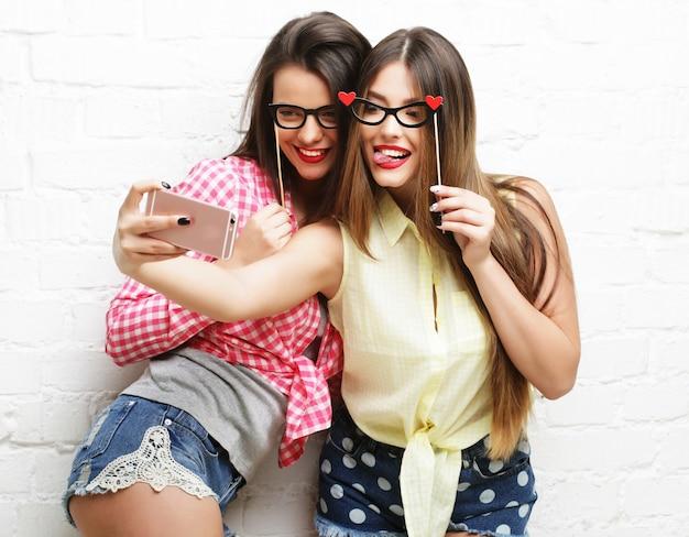 Selfie를 복용 파티 안경 두 젊은 행복 한 여자