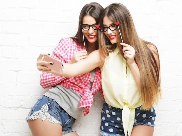 Selfie を取ってパーティー メガネを持つ 2 人の若い幸せな女性