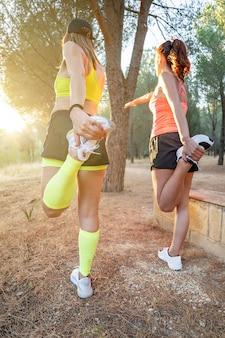 뒤에서 공원 보기에서 달리기 전에 다리를 기지개하는 2명의 젊은 건강한 피트니스 여성 주자