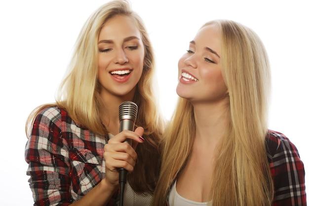 2 つの若い流行に敏感な金髪の女の子が白で歌っています。