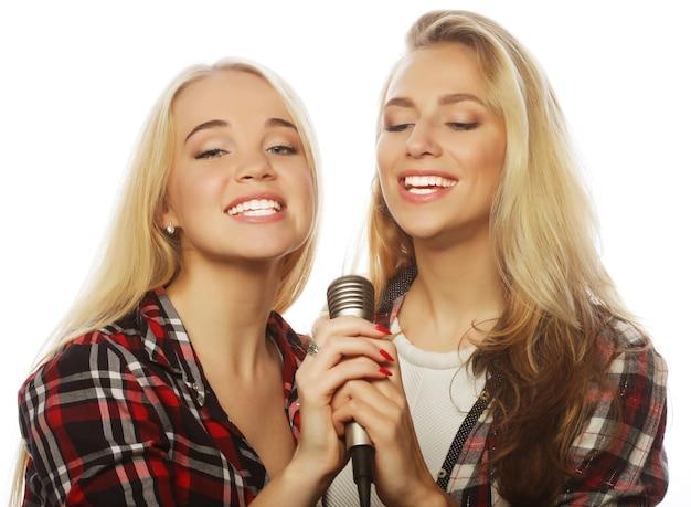 흰색 배경 위에 노래하는 두 젊은 힙스터 금발 소녀