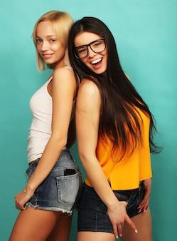 Две молодые хипстерские подруги стоят вместе и веселятся на синем
