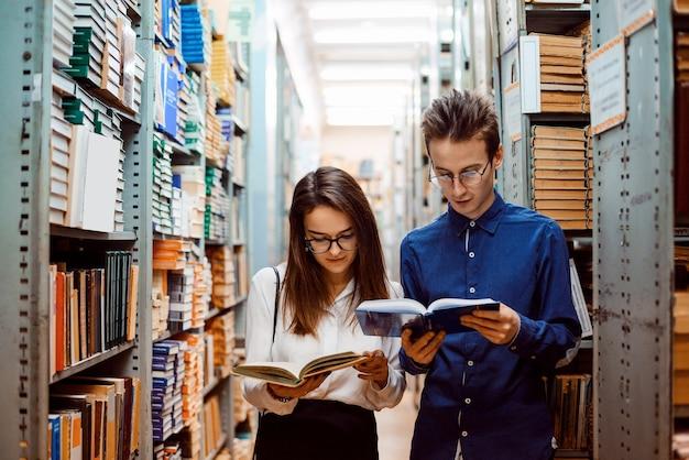 Двое молодых студентов-историков в очках исследуют базу данных городского архива