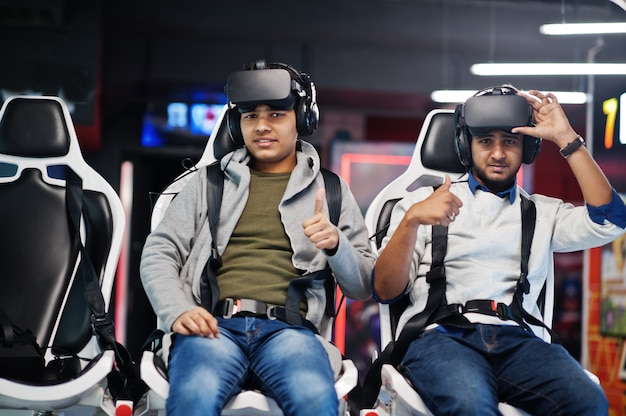 Two young indian people having fun with a new technology of a vr headset at virtual reality simulator they happy and show thumb up