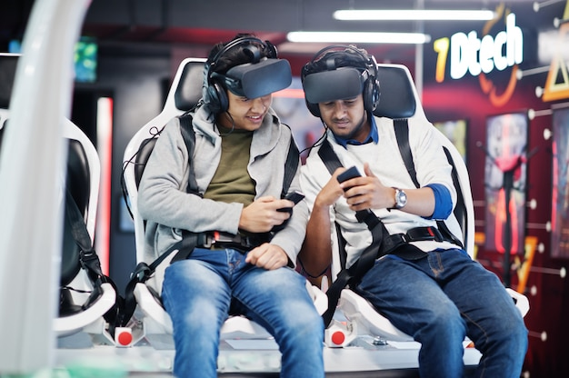 Two young indian people having fun with a new technology of a vr headset at virtual reality simulator with mobile phone at hands