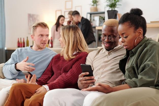 ソファに並んで座って、モバイルガジェットのソーシャルネットワークで写真について話し合うスマートカジュアルウェアの2人の若い異文化カップル