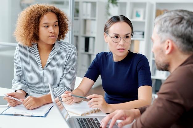 Две молодые межкультурные подчиненные консультируются со своим начальником по вопросам нового проекта на стартовой встрече