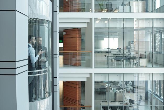 사무실이있는 대형 현대식 비즈니스 센터 내부의 엘리베이터에서 위쪽으로 이동하면서 대화를 나누는 두 젊은 이문화 관리자