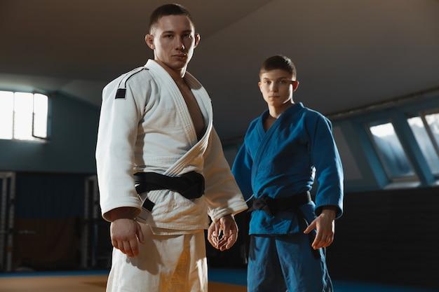 白と青の着物を着た 2 人の若い白人の柔道選手が、黒帯を着てジムで自信を持ってポーズをとって、強くて健康的です。