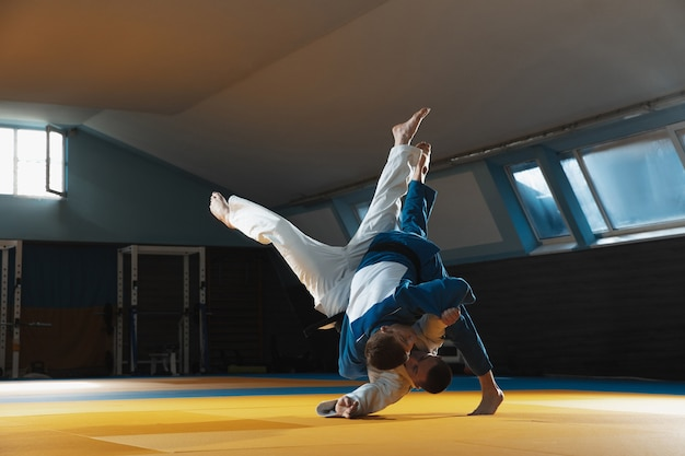 Two young judo caucasian fighters in white and blue kimono with black belts training martial arts