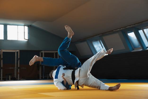 体育館で武道を訓練する着物姿の2人の若い柔道選手が、動きと動きを表現しています。