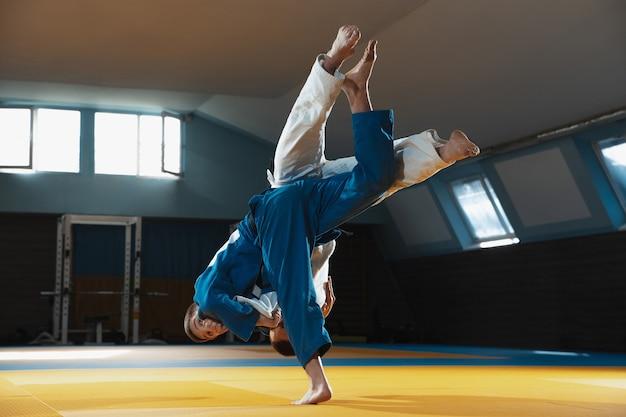 행동과 움직임의 표현으로 체육관에서 무술 훈련 기모노 두 젊은 유도 전투기