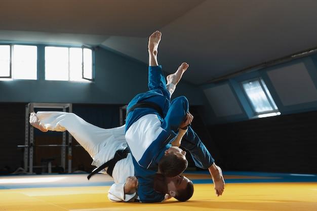 体育館で武道を訓練する着物の2人の若い柔道の戦闘機