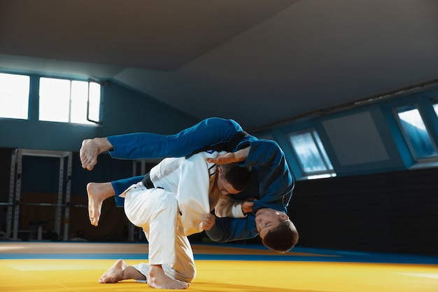 Two young judo fighters in kimono training martial arts in the gym with expression in action and motion