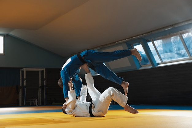 Two young judo fighters in kimono training martial arts in the gym with expression, in action and motion