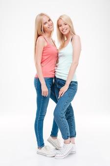 두 젊은 숙녀 티셔츠와 청바지 포즈를 입고. 흰 벽 위에 절연. 앞을보고.