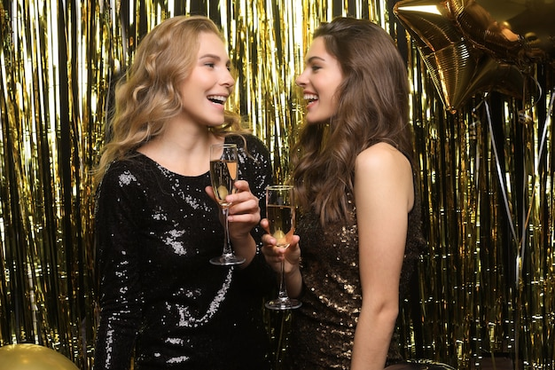 Two young ladies drinking champagne. image of girls with balloons isolated on gold background.