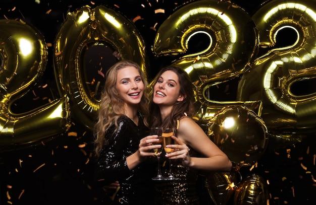 샴페인을 마시는 두 젊은 여성. 검은 배경에 풍선을 들고 크리스마스나 2022년 새해 이브 파티에서 즐거운 시간을 보내는 소녀들의 이미지.