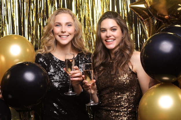 シャンパンを飲む2人の若い女性。金色の背景に分離された風船を持つ女の子の画像。