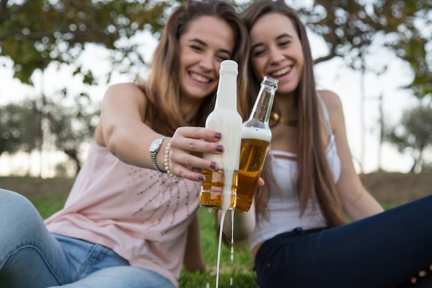 Two young laughing women in park toasting with beer bottles having fun.