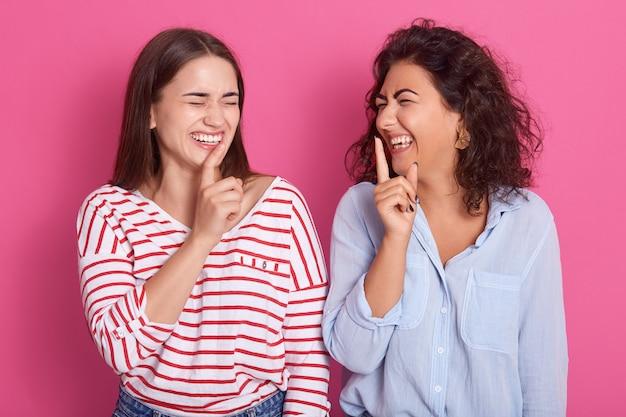 黒髪の2人の若い笑う女性、指を口に当て、カジュアルなシャツを着て、一緒に楽しんで