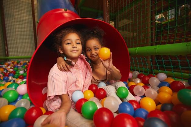 Две молодые маленькие девочки играют вместе с мячами в парке развлечений