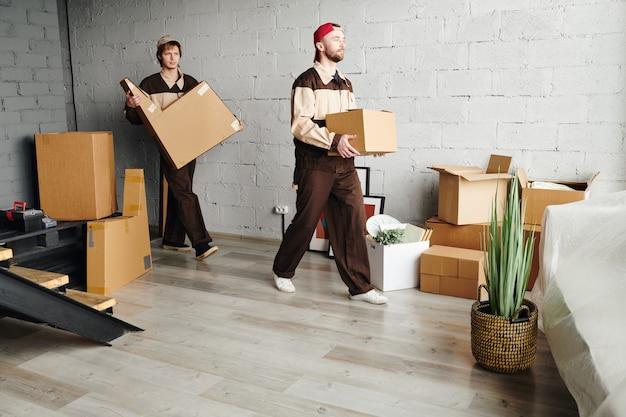 Двое молодых грузчиков в спецодежде несут упакованные картонные коробки, помогая доставлять посылки в новую квартиру, дом или студию