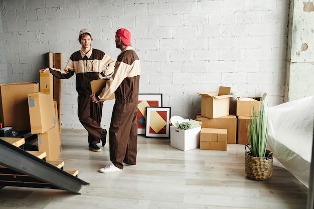Двое молодых грузчиков в спецодежде доставляют упакованные картонные коробки, помогая людям переехать в новую квартиру, дом или студию