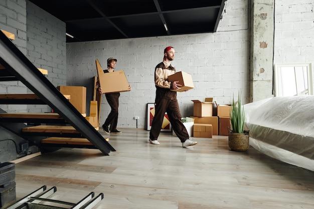 Двое молодых грузчиков в спецодежде входят в большую комнату или студию и несут упакованные картонные коробки, помогая доставлять посылки
