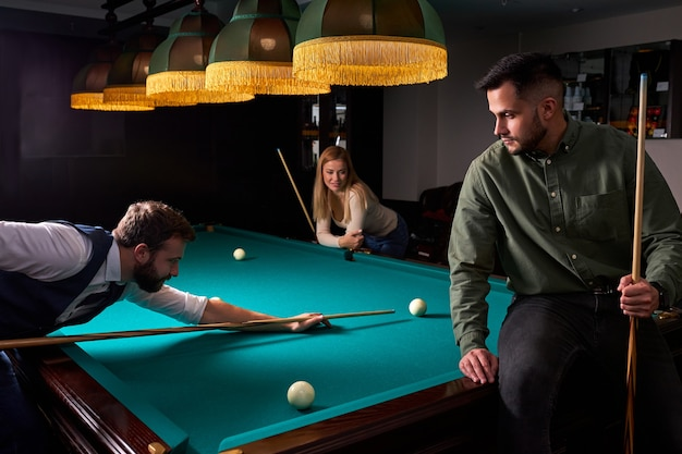 Двое молодых друзей-мужчин пришли поиграть в бильярд или снукер в темном клубе после работы