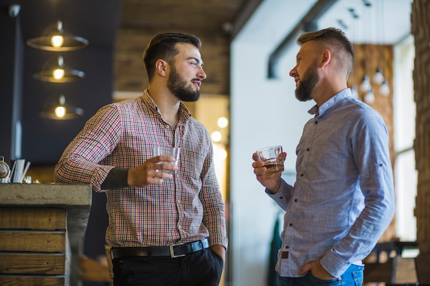 Two young male friends holding glass of drinks standing at bar counter