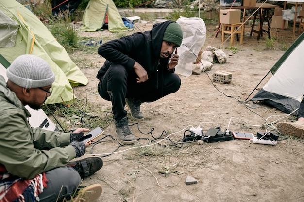 スマートフォンを使用して2人の若い男性難民