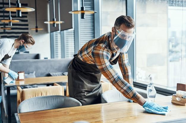 Двое молодых мужчин-официантов в защитной спецодежде чистят столы в ресторане